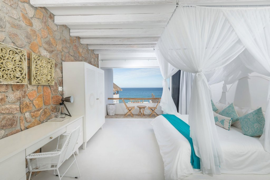 Boutique hotel room with large bed and stone wall - Casa Tara Retreat